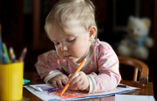 A baby coloring with a marker