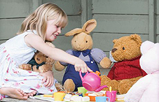 Girl having tea party with stuffed animals