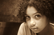 Young girl with curly hair has expressionless face