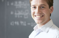 Man smiling in front of a chalkboard