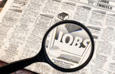 Jobs section in a newspaper with magnifying glass