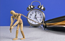 Wooden doll pulling a clock and folder