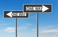 """One Way"" signs pointing in opposite directions"