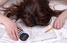 Woman with head buried in tax papers