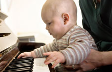 Baby on lap playing piano