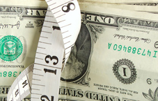 Measuring tape wrapped around dollars