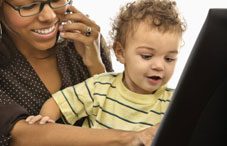 Mother on laptop with baby in lap