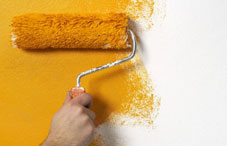 Person painting wall yellow