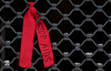 "A ""Stop Aids"" ribbon tied to a gate"