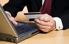 Man typing information from credit card
