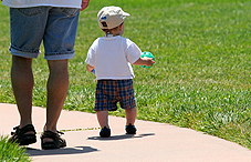 Baby and adult walking on sidewalk