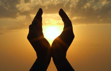Silhouette of divine hands in sunset
