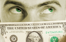 Man with green eyes looking over dollar bill