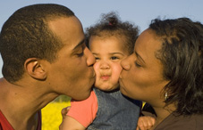 Family kissing baby