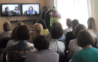 A group of therapists gathered in the training room to watch Simakhodskaya (on screen) conduct a live EFT therapy session