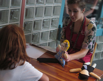 "A ""Teen Psych"" participant presents a hands-on child development activity for families visiting the Discovery Center (activity based on Widen & Russell, 2010)"