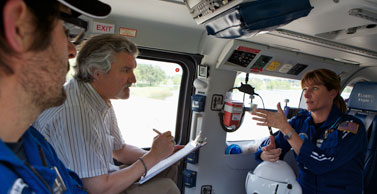 Dr. Salas sits in a helicopter with pilots.